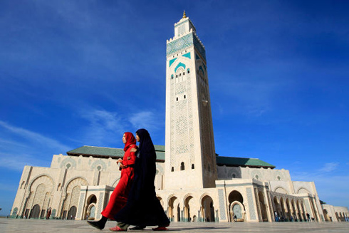 Two women walk past the Hassan II mosque in Casablanca, Morocco, in 2011. The minaret of the mosque is the highest in the world, standing at 689 feet. Moroccan women are studying to be religious leaders, the female equivalents of imams, who would reject religious extremism. Image: Pascal Rossignol/Reuters/File