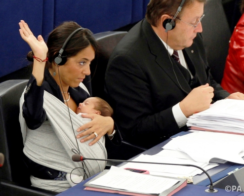 Mother working on EU parliament with baby