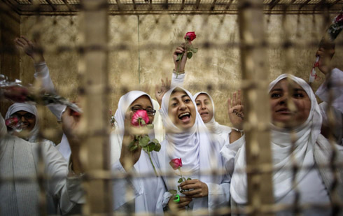 Women wearing hijabs and holding roses.