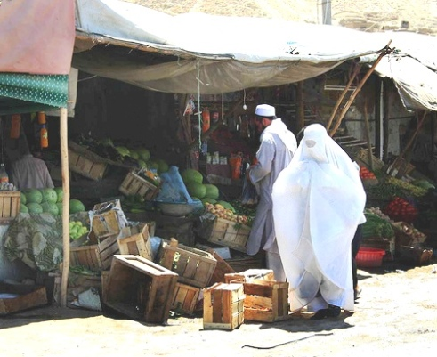 Afghan woman wears burka as she shops at market