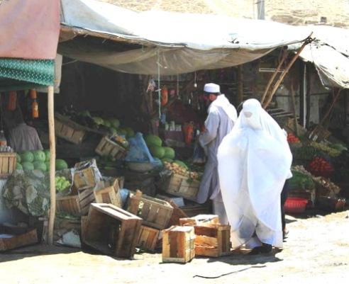 Afghan woman wears burka as she shops at market