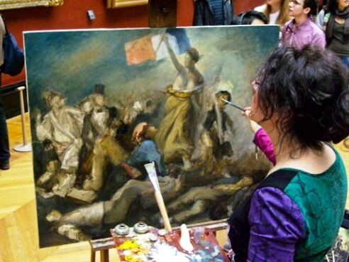 Female artist painting at the Louvre Museum in Paris