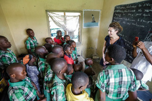Woman speaks to children in their classroom