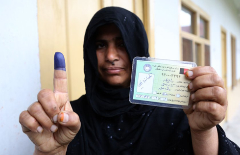 An Afghan woman shows her inked finger after voting in Jalalabad