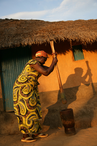 A woman pounds manioc (cassava) leaves in preparation of a cooking a meal for the family.