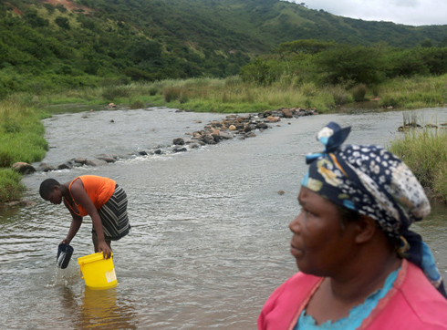 Women gathering water from river.