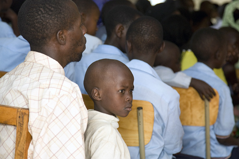"""Rwanda father and son join other men and boys in  the audience of the arrival of Secretary-General Ban Ki-moon and Mrs. Ban to the """"Village of Hope"""" Project."""