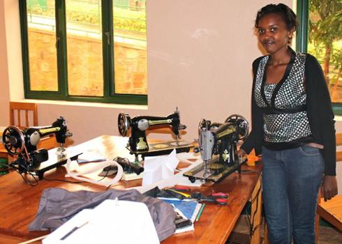Colombe Ndutiye Ituze stands in front of her work desk