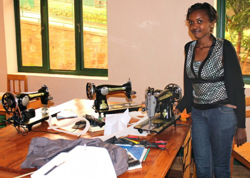 Colombe Ndutiye Ituze stands in front of her work desk