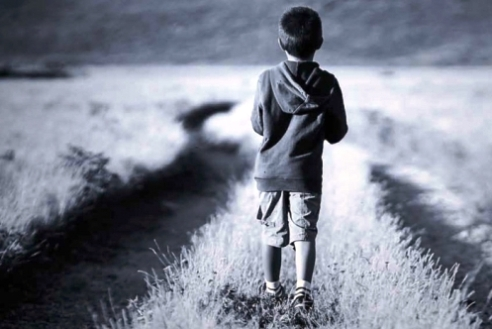 Migrant boy walking in field