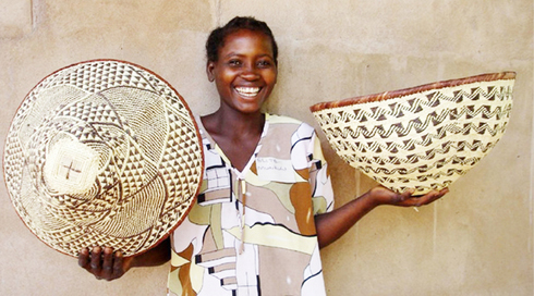 Grace Madekurozva holding 2 weaved baskets