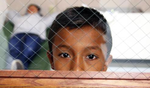 Boy migrant in holding cell